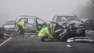 A Thames Valley Police collision investigator takes notes by damaged vehicles on the A40 near Witney, Oxfordshire, after a woman died following a pile-up which involved around 20 vehicles.